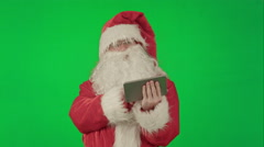 Cheerful Santa Claus is holding a tablet in his hands on a Green Screen Chrome Stock Footage