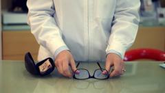 Optician showing a new pair of glasses to a client - stock footage