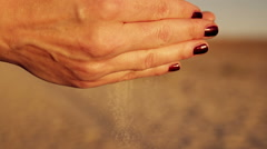 Female hands  sypyat sand at sunset in the sun - stock footage