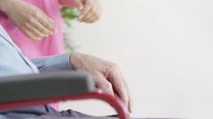 4K Caring home support worker holding the hand of elderly man in wheelchair Stock Footage