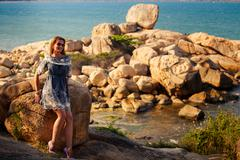 girl in short grey frock stands on rocks by sea against city - stock photo