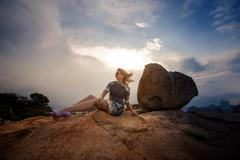 Brunette girl in short grey frock sits on rock against sky Stock Photos