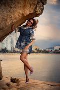 brunette girl in short frock high-heel shoes stands under rock - stock photo