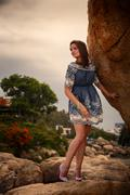 brunette girl in short frock high-heel shoes stands under rock - stock photo