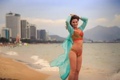 brunette girl in bikini transparent frock stands tip-toe on sand - stock photo