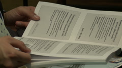 Man flips through handbook at conference Stock Footage