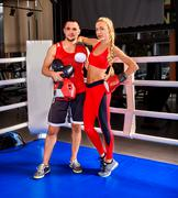Stock Photo of Female boxer in red with your male coach after workout
