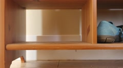 A man places his shoe into a shoe organizer in the house - stock footage