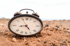 Classic Analog Clock In The Sand Stock Photos