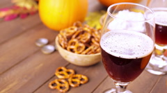 Craft pumpkin beer in beer glasses with salty pretzels and popcorn. - stock footage