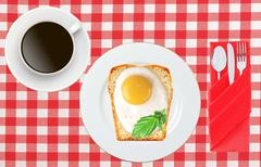 Scrambled eggs with bread on plate on color napkin and coffee cup - stock photo