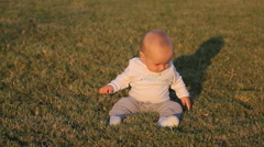 Little boy sitting on the grass - stock footage