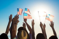 Young people waving American flags at sunset. - stock photo