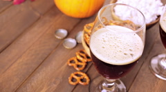 Craft pumpkin beer in beer glasses with salty pretzels and popcorn. Stock Footage
