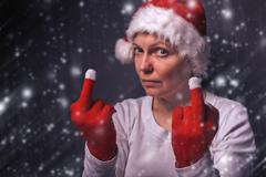 Beautiful woman in Santa Claus costume giving middle finger - stock photo