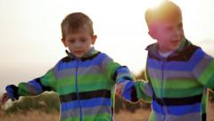 Two little kids running nature beautiful countryside grass meadow slow motion - stock footage