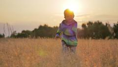 Cute little boy running beautiful nature sunset golden meadow nature slow motion Stock Footage