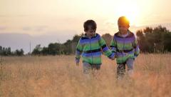 Two little boys walk grass meadow nature countryside sunset slow motion Stock Footage