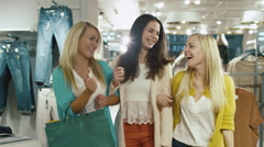 Three happy girls are walking through a clothing store in colorful garments - stock footage