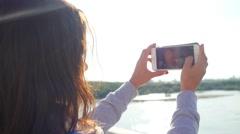 Beautiful woman taking pictures of her self, instagram, selfie on the bridge in Stock Footage