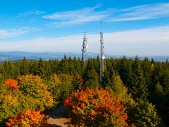 Two transmission towers in autumn forest Stock Photos