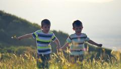 Two little kids running nature beautiful countryside grass sunny day slow motion - stock footage