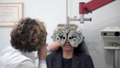 Eyesight Exam In Clinic with female doctor and female patient Stock Footage