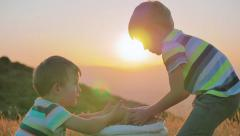 Two kids play with golden wheat grains slow motion countryside scenery Stock Footage