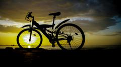 Stock Photo of Silhouette of mountain bike with sunset sky at sea