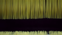 Raw spaghetti hanging to dry up in a pasta factory. - stock footage