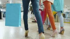 Low shot of female legs walking through a department store in colorful garments - stock footage
