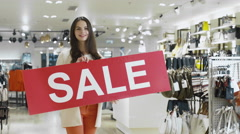 Stock Video Footage of Young smiling brunette girl is holding a sale sign in a department store