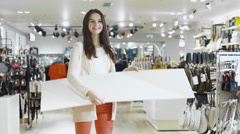 Young smiling brunette girl is flipping a sale sign in a department store Stock Footage