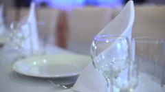 Several glasses and plates on table with a white tablecloth Stock Footage