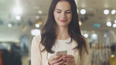 Happy young brunette girl is standing in a store and texting on a smartphone - stock footage