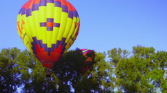 Hot air balloon stays close to a row of trees Stock Footage