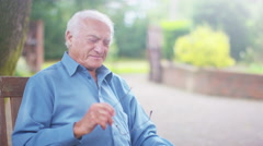 4K Portrait of cheerful elderly man using a computer tablet in the garden Stock Footage