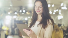 Happy young brunette girl is standing in a department store and using a tablet - stock footage