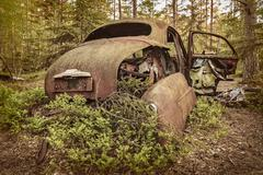 Old rusted scrap car in a forest - stock photo