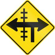 New Zealand road sign - Level crossing on controlled T-junction on left - stock illustration