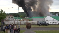 Black smoke rise from warehouses fire fighters fight fire. 4K Stock Footage