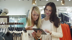 Two happy young girls are shopping clothes and checking a tablet in a store Stock Footage