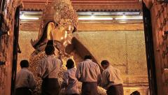 Believers worship Buddha statue,paste gold leaf petals at Mahamuni Buddha temple Stock Footage