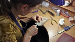 girl jeweler chamfering the billets for silver ring, with a file(tool), - stock footage