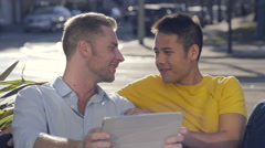 Man Reads Aloud From His Tablet, His Asian Boyfriend Listens/Laughs Stock Footage