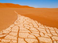Cracked soil and red sand of Namib desert in Namibia Stock Photos