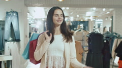 Happy young brunette girl is walking though a clothing store Stock Footage