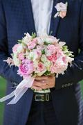 groom hold wedding bouquet in hand - stock photo