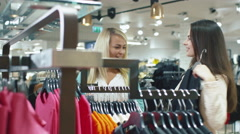 Two happy young girls are choosing garments in a department store - stock footage