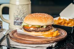 Cheeseburger served  with French Fries and Beer Stock Photos